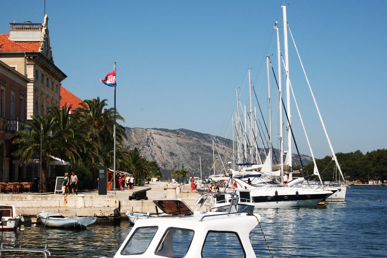 vanaf het terras kun je de boten zien liggen afgemeerd in de haven langs de kade in Starigrad