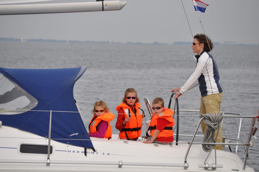 Kinderen tijdens hun zeilweekend met ouders aan boord van onze Harmony 34, allemaal met zonnenbril en reddingsvest. Oranje is best mooi zeker met zonnenbril